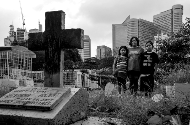 Lenlen Breva stands with her children Jennalene, 9, and Joni, 12, in Manila's South Cemetery. August, 2010.  Photos Copyright © 2010/Kim Komenich. All rights reserved.